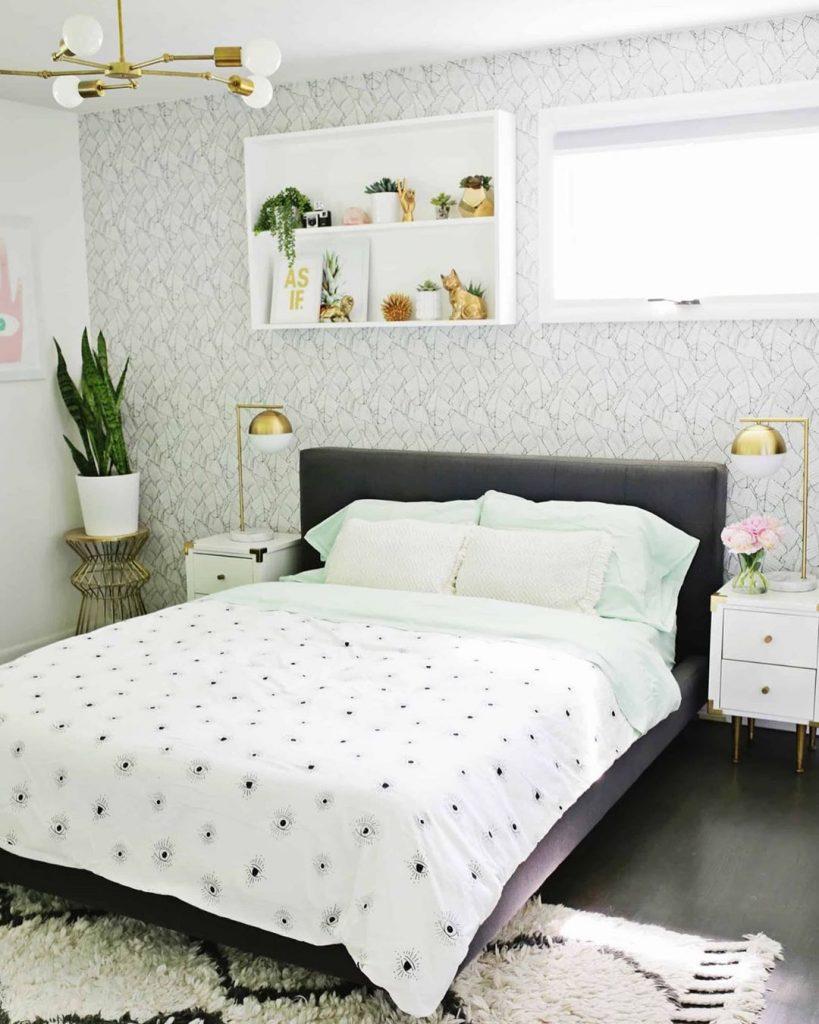instagram de decoração cama com cabeceira preta, abajours dourados, prateleiras acima da cama brancas, lençol branco, planta no quarto