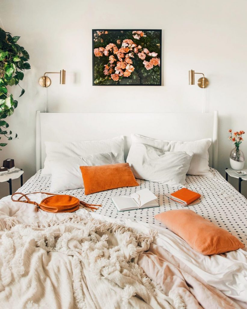 instagram de decoração cama branca com travesseiros laranjas, quadro acima da cama com flores, abajours dourados