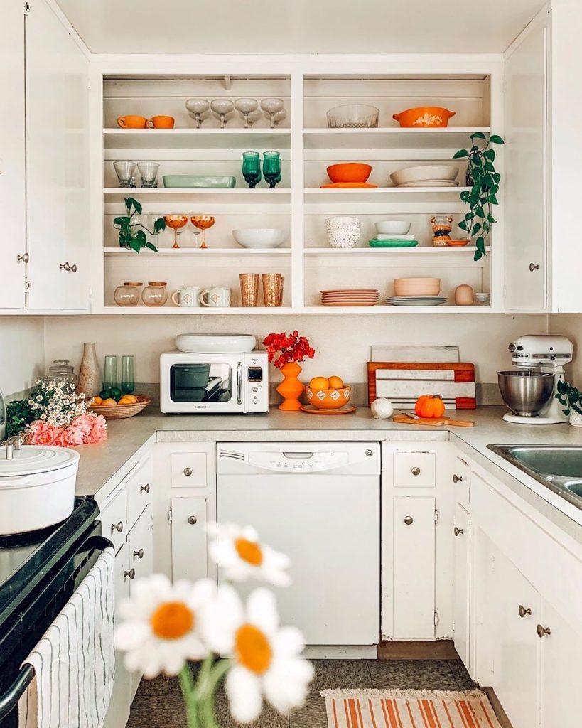 instagram de decoração - cozinha branca com itens laranja e branco na prateleira e armários superiores, eletrodomésticos e decoração laranja e branco