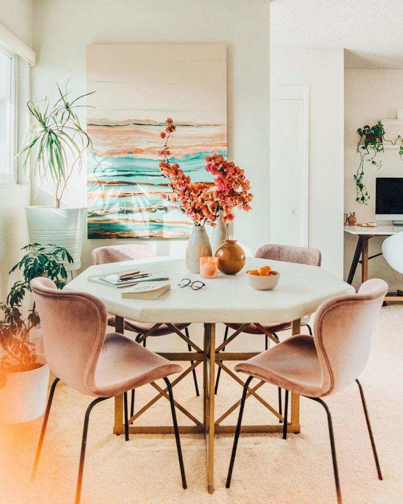 instagram de decoração - sala de jantar com mesa redonda e cadeiras rosa, quadro na parede com flores ao redor