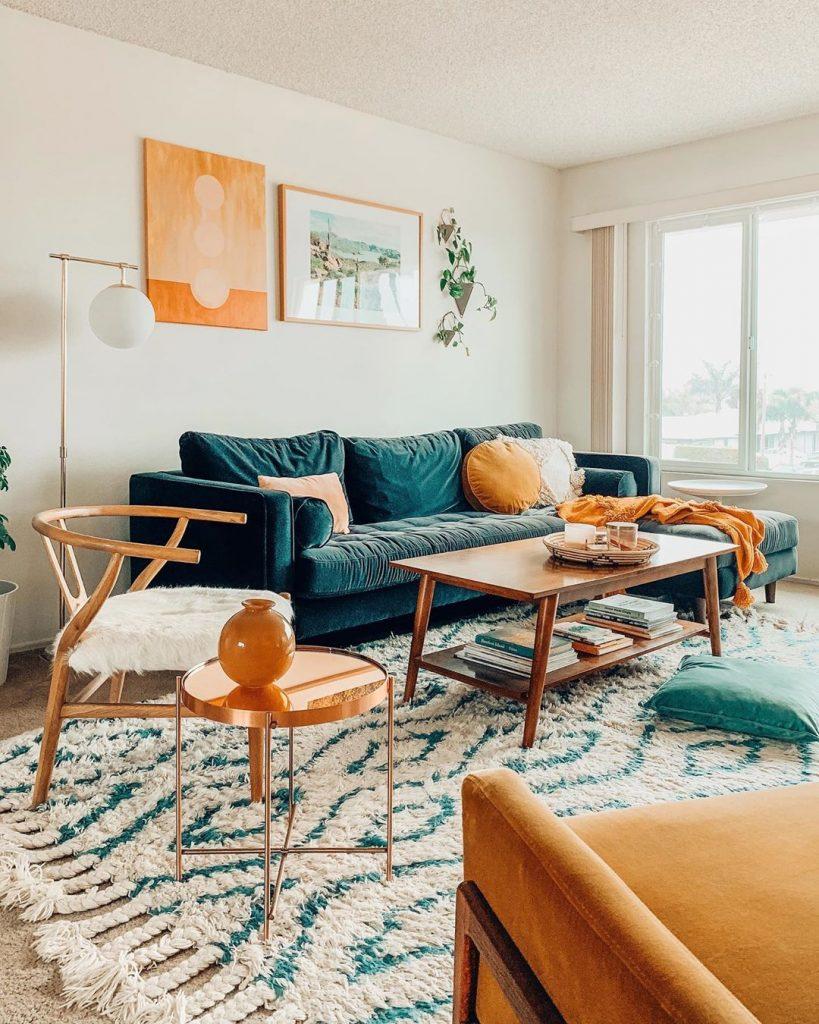 instagram de decoração - sofá azul na sala, com quadros e planta, cadeiras e tapete, mesa de centro de madeira