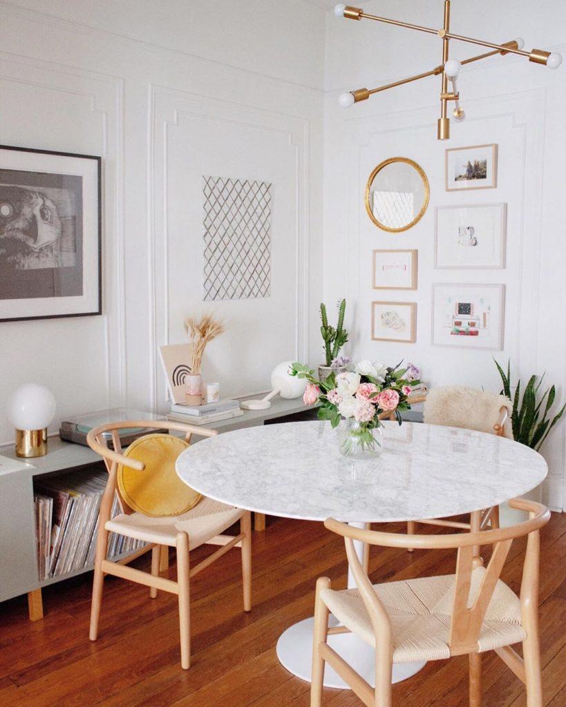 instagram de decoração - sala de jantar com mesa branca e cadeiras de madeira, parede com quadros dourados e chão de madeira