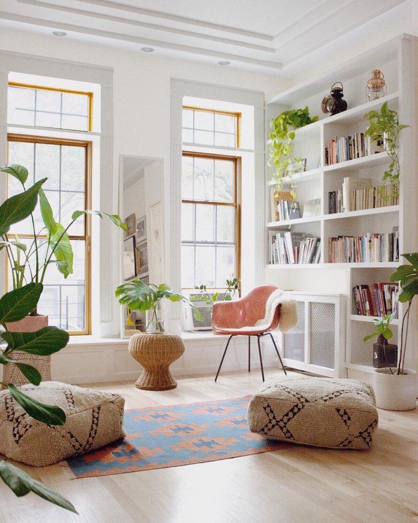 instagram de decoração - estante com livros, biblioteca em casa, tapete e puffs, plantas verdes em vários lugares