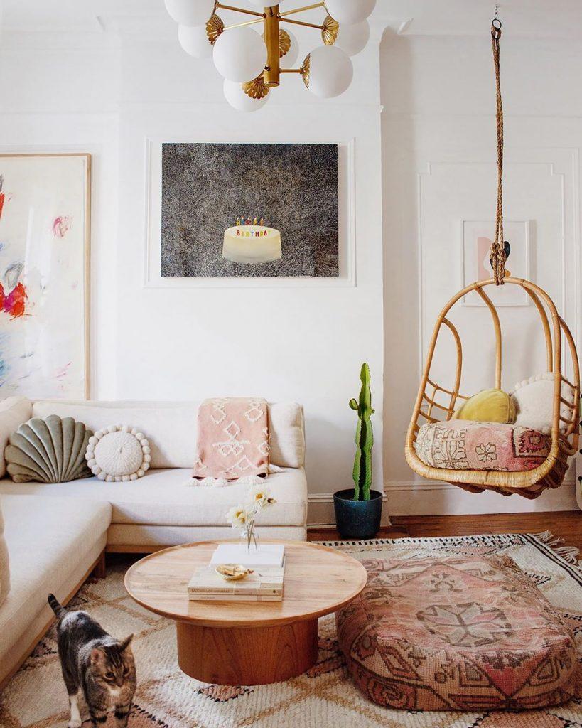 instagram de decoração - cadeira pendurada, sofá na sala branco, tapete colorido, mesa de centro de madeira, parede branca com quadro