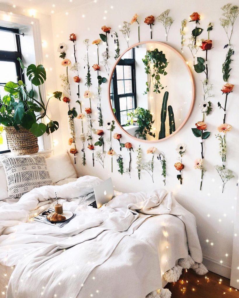 instagram de decoração espelho na parede, quarto, cama com cobertas e flores penduradas ao redor do espelho na parede