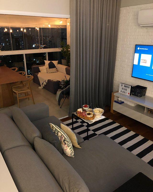 sala com televisão ligada, mesa de centro com comidas, sofá, varanda à vista, para spa em casa