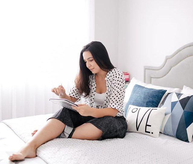 tarefas de casa sendo planejadas com mayara sentada na cama e usando tablet